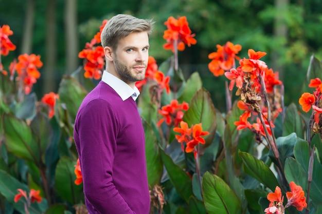 Человек, стоящий открытый на весеннем цветочном фоне, мужская красота.