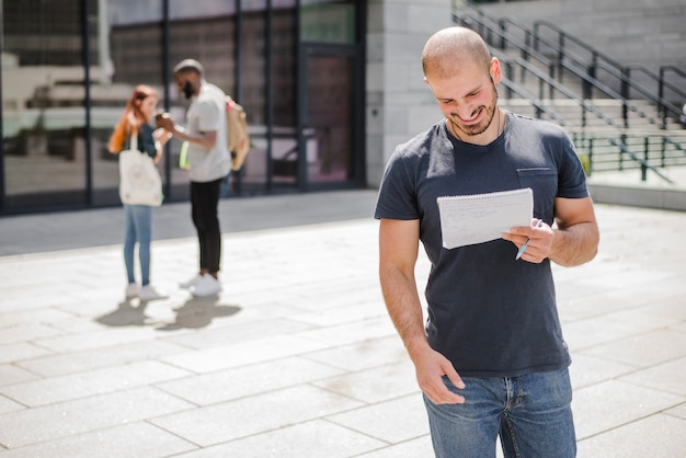Man standing outside holding notepad smiling