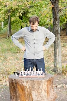그의 체스 전략을 계획하는 삼림 지대의 소박한 로그 테이블에 체스 판 위에 서있는 남자 프리미엄 사진