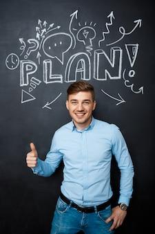 計画概念の親指で黒板の上に立っている人