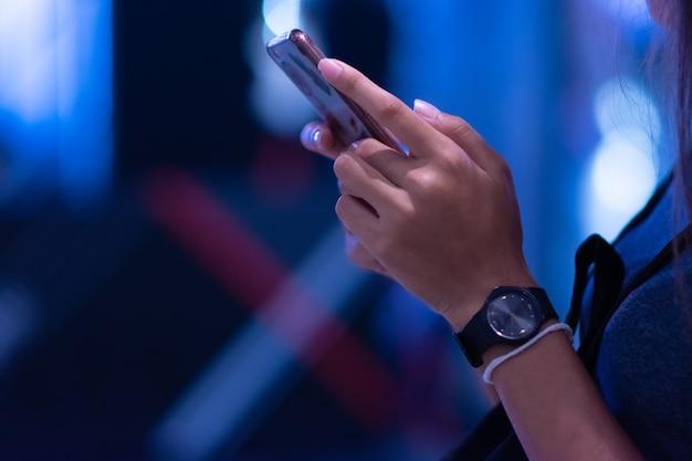 Человек, стоящий, играя с телефоном и размытым фоном