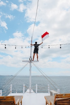 A man standing on pole ship and waving indonesian flag