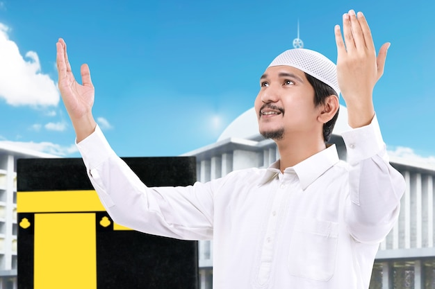 Man standing and praying with kaaba view and blue sky background