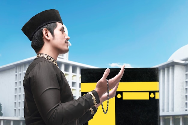 Man standing and praying with prayer beads with kaaba view and blue sky background