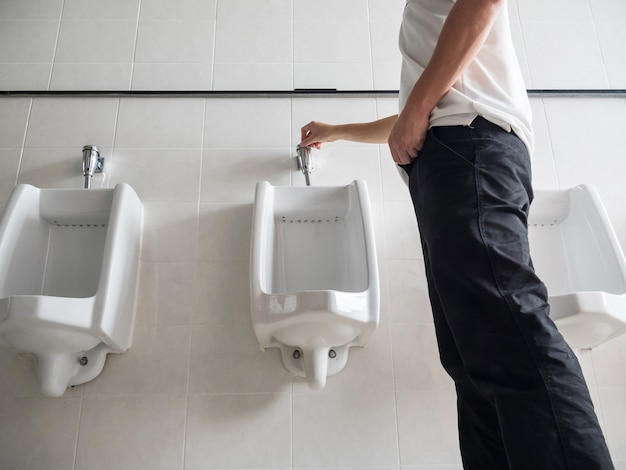 Man standing press flushing a urinal in a public washroom