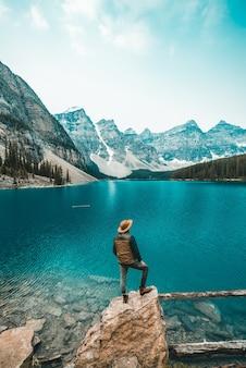 Uomo in piedi sulla roccia vicino al lago