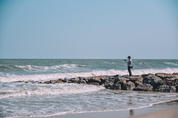 Man standing on rock view on beach and sea