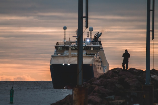 Man standing on rocks overlooking ship on body of water