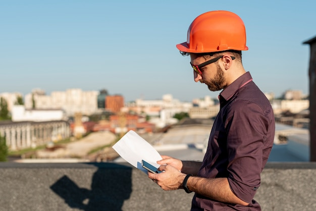 Man standing on rooftop with phone in hand