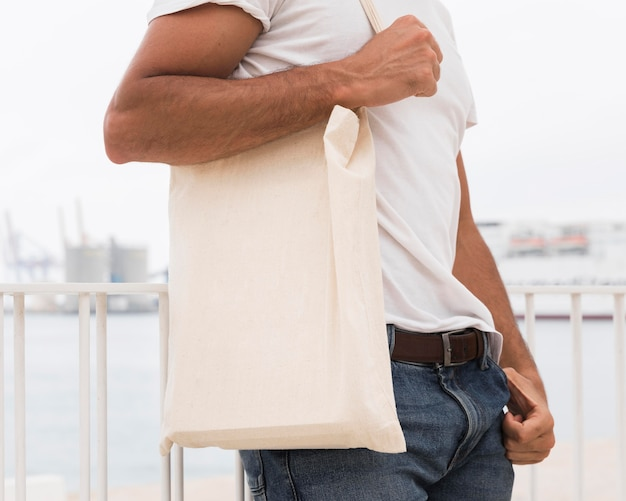 Man standing next to the sea holding white bag