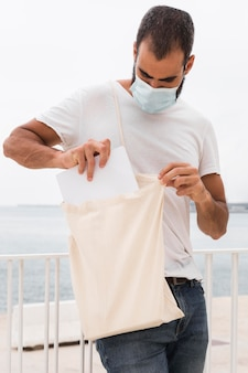 Man standing next to the sea holding white shopping bag