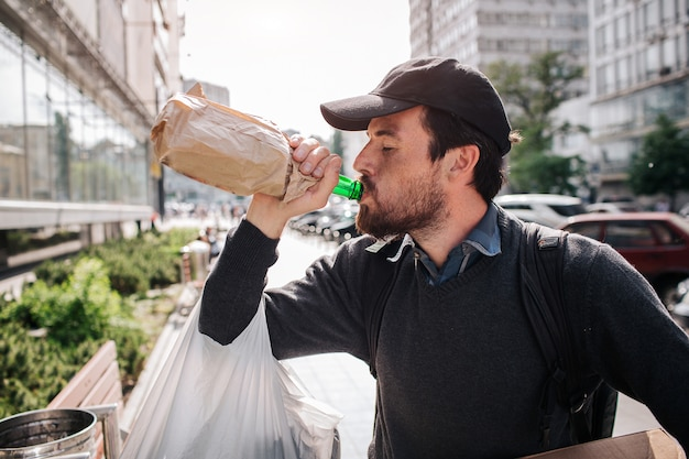 Man standing on the street and drinking from bottle