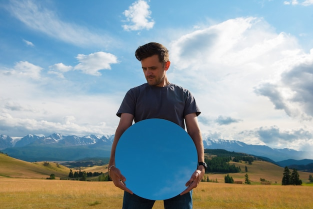 Man standing in in summer altai mountains in kurai steppe and holding circle mirror creative travel ...