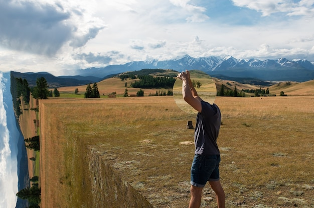 Man standing in in summer altai mountains surreal landscape and holding circle mirror creative trave...