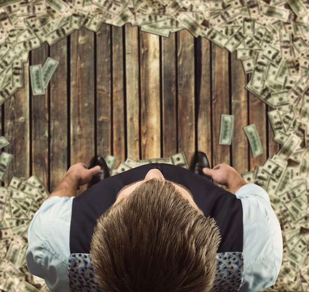 Человек, стоящий в окружении долларов