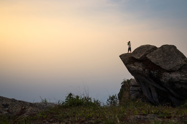 The man standing and take photo on cliff. a man stands on top of a rocky outcrop.