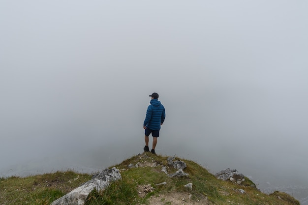 Man standing on top of mountain admiring landscape with fog