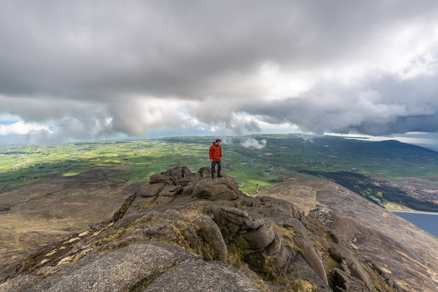 Man standing on the top of  mourne mountains northern ireland