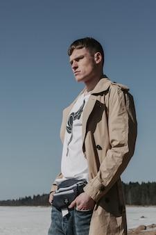 ベージュのトレンチコート、白いtシャツ、ウエストパック、ブルージーンズで太陽光線の下に立っている男。