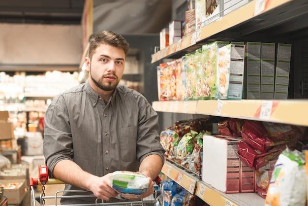 スーパーマーケットの通路にカートで立っている男性