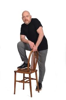 Человек, стоящий со стулом на белом фоне