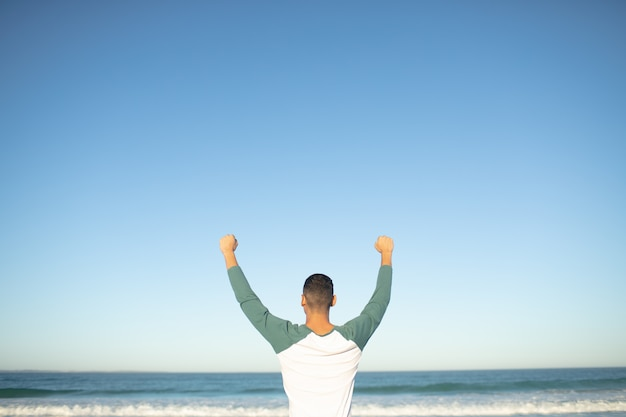 Man standing with arms up on the beach