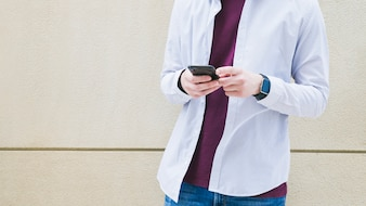 Man standing with cell phone in front of concrete wall