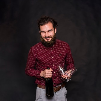 Man standing with champagne bottle and glasses