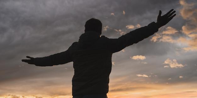 Человек, стоящий с широко открытыми руками под пасмурным вечерним небом