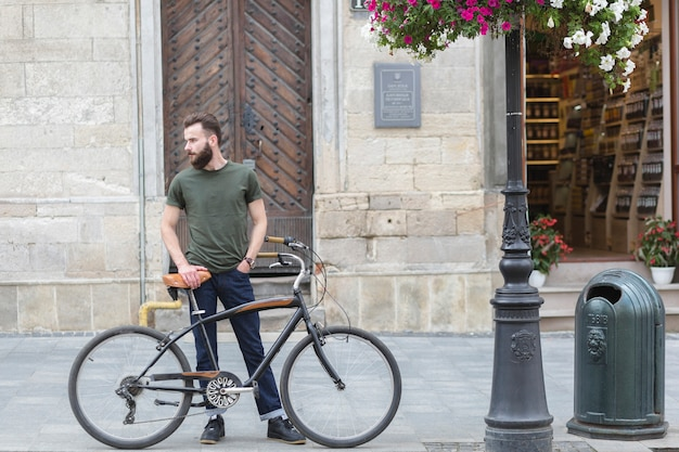 Man standing with his bicycle on pavement
