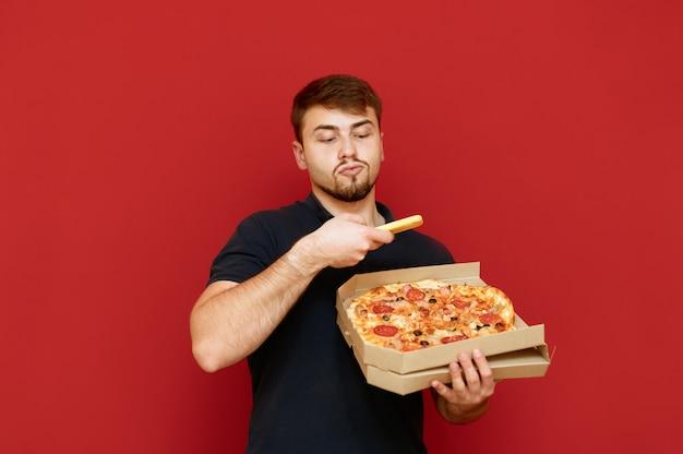 Человек, стоящий с коробкой для пиццы в руке и фотографирующий