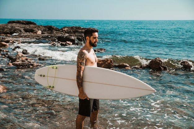 Man standing with surfboard in blue water