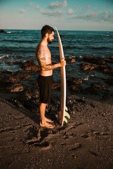 Man standing with surfboard on sea shore
