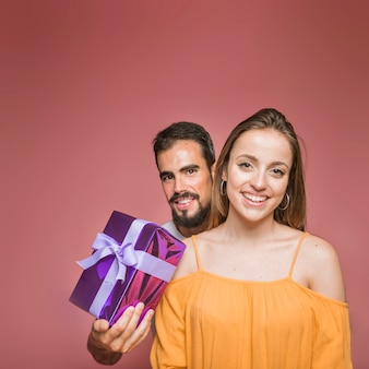 Man standing behind the woman holding present on colored background
