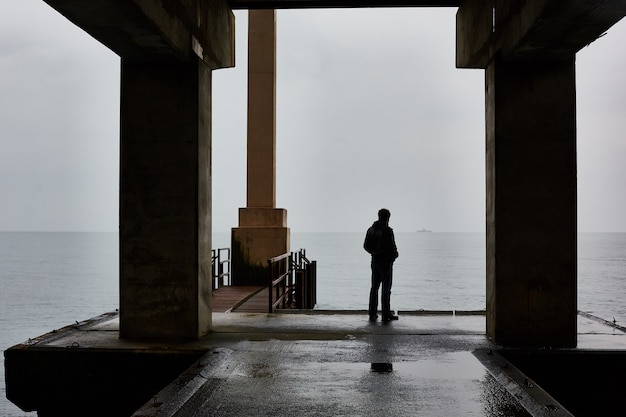 Man stands alone on a pier of sea in bad weather. foggy air.