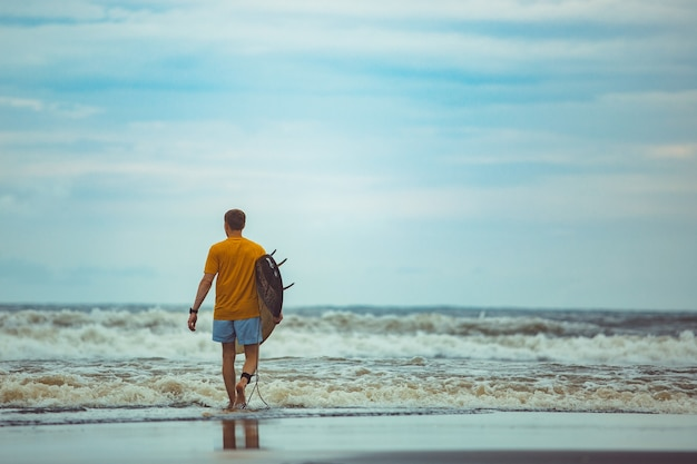 A man stands on the beach with a surfboard.