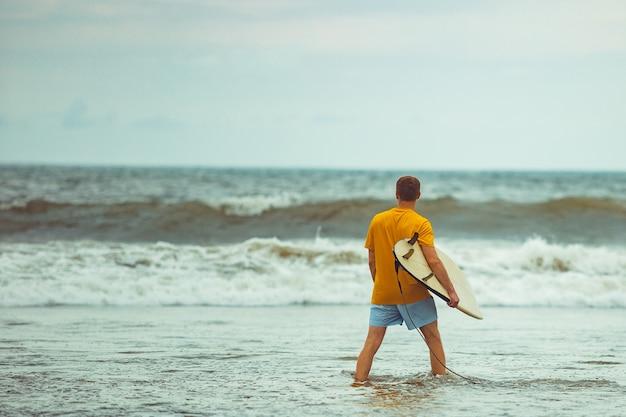 Un uomo sta sulla spiaggia con una tavola da surf.