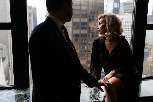 Man stands before a stunning woman looking through the panoramic window at new york streets