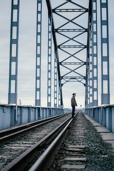 Man stands bored on rails of an old railway bridge, sadly waiting for a meeting. industrial landscape. big iron bridge on a cloudy day. the concept of separation, meeting, depression. copy space