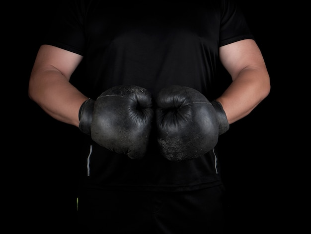 Man stands in a boxing rack, wearing very old vintage black boxing gloves