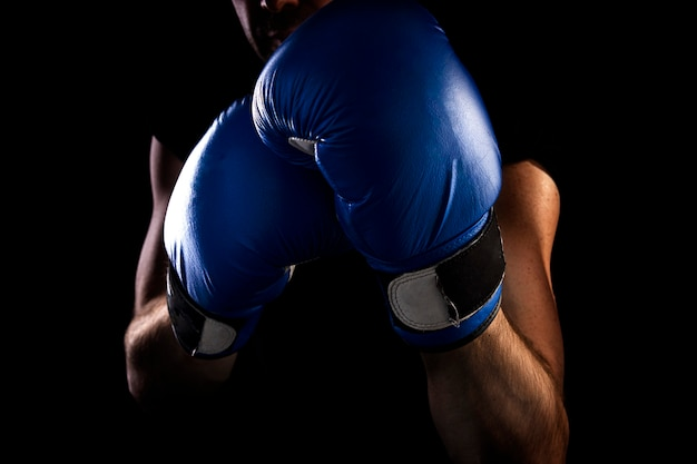 Man stands in boxing stance, holds blue boxing gloves on his hands, dark background