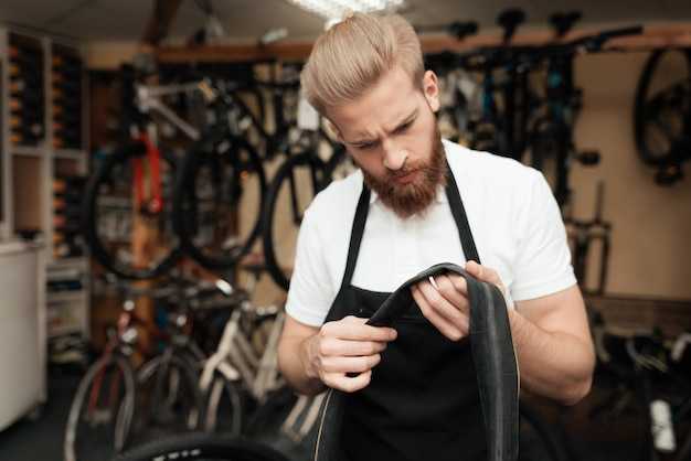A man stands and carefully inspects the detail of the bike.