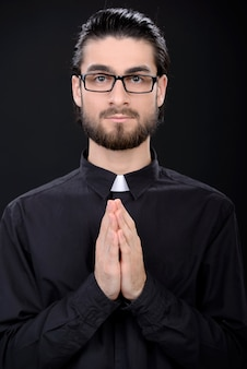 A man stands in glasses and folded his arms together.
