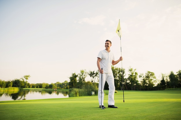 A man stands on a golf course, holds a golf club and flag