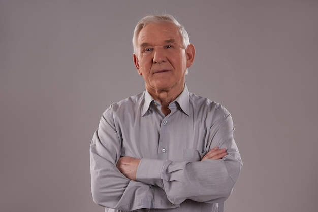Man stands on gray background with crossed arms