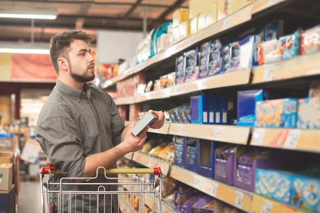 Мужчина стоит в супермаркете с пачкой печенья в руках и смотрит на полку со сладостями