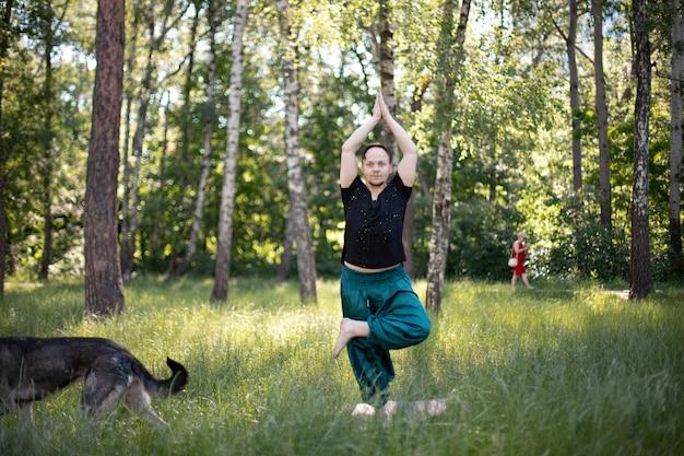 Мужчина стоит в асане, практикуя йогу в парке на зеленой траве. международный день йоги