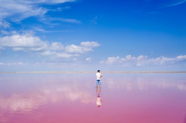 男は塩辛いピンクの湖の真ん中に立っています