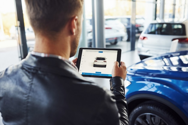 Man stands inside car salon with tablet in hands and looks at the vehicle picture.