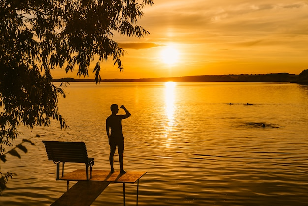 A man stands on a masonry near the lake and looks at the sunset.
